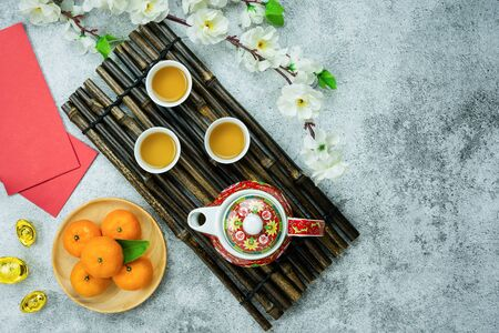 Chinese language mean rich or wealthy and happy.Top view of Lunar New Year & Chinese New Year vacation concept background.Fresh orange & cup of tea with pink cherry flower and gold on grey cement.