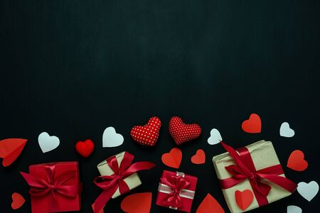 Table top view image of decoration valentine's day background concept.Flat lay arrangement of red shape & gift box with essential items on modern rustic black wood with middle space for mock up design 版權商用圖片