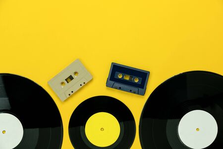 Table Top view of musical instrument retro concept.Flat lay objects of the many music disk and  cassette tape on modern rustic yellow paper at home office desk.copy space for creative design text.
