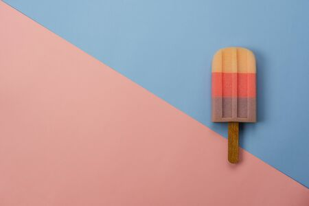 Table top view aerial image of sign or food of summer season holiday background concept.Flat lay of pastel ice cream on modern rustic pink  & blue paper backdrop.Minimalism creative design. copy space