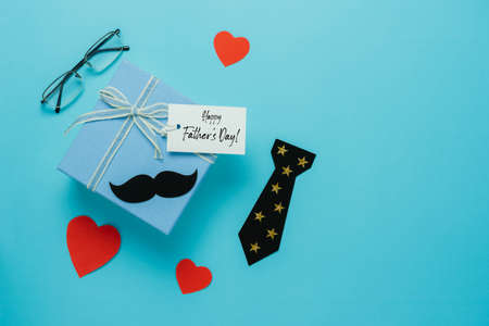 Table top view Happy Fathers day holiday background concept.Flat lay  gift  box for dad with accessories objects sign of season the wallet,Gift box & love heart and greeting card on blue paper.