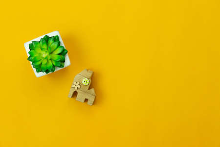 Table top view of  home kids toy wooden & tree pot on yellow paper background.Safe stay at home for social distancing of coronavirus (covid-19) or homeless loan concept. Family international day, 免版税图像
