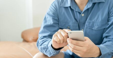 Young man hand holding mobile phone device.