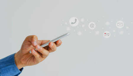Business & Technology lifestyles background concept.Close up young Asian man wear white shite holding smart phone checking the email online website with email icon on white backdrop.copy space. 免版税图像