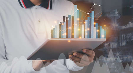 Close up Businessman wear white shirt using tablet for checking business growth up or stock market with data statistics level up of graph or chart.Financial & Technology concept ,planning and strategy