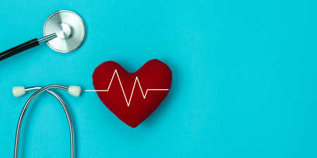 Table top view aerial of accessories healthcare & medical background concept.Red heart & stethoscope with design heart wave on blue paper.Flat lay of idea for doctor treat & care patient in hospital. Banque d'images