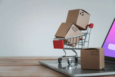 Close up Paper cartons with a shopping cart or trolley on a laptop. Ideas about customers order buy from retailer sites via the internet website.Online shopping,ecommerce and delivery service concept