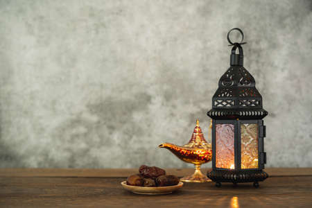 On table top image of decorations Ramadan Kareem holiday background.Close up Arabic lantern metal on brown wooden and aladdin lamp or arabic lantern.Halal meal set for fasting is obligatory for Muslim