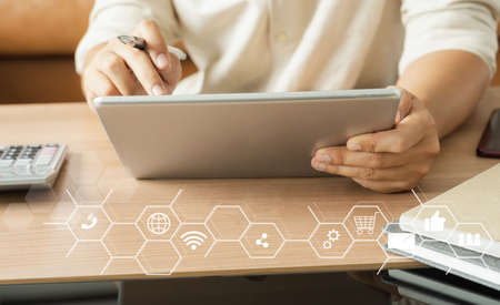 Business man wear white shirt using tablet for digital online marketing on office desk. Business finance technology concept. Icon online e-commerce global market shopping, banking and payments.