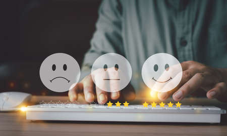 Hand using keyboard with Happy icon and Five stars for service rating feedback of experience customer survey. Business annual satisfaction  concept. Many sad or happily icons, excellent performance. 免版税图像