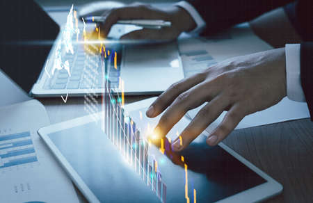 Close up Businessman working on table office deck for business growth up or stock market with data statistics level up of graph or chart.Financial and Technology concept ,planning and strategy icon.