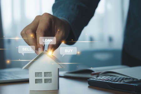 Businessman holding model house paper with message detail. Real estate property investment, mortgage agent offer, bank home loan for housing ownership, Business and Finance insurance concept.