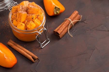 Persimmon jam or marmalade with cinnamon in glass jar on brown background in dark mood style with copy space - close up photography of organic sweet dessert with fragrant spice. Banque d'images - 116474262