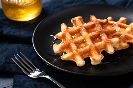 Freshly prepared belgian waffles with honey or maple syrup on black plate on dark blue background - close up horizontal photography of homemade crispy baked sweet dessert for breakfast. 스톡 콘텐츠