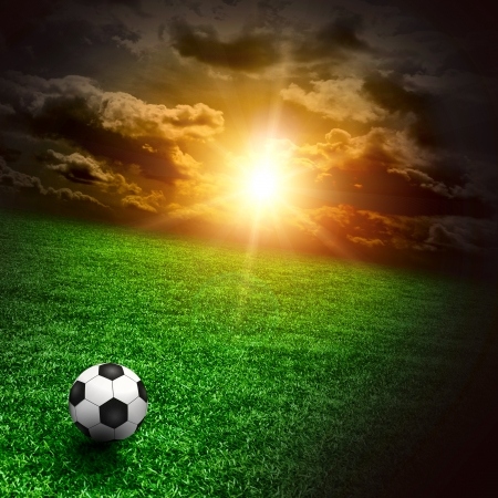 soccer background: A fine green meadow with a soccer ball on it  All on sky sunset