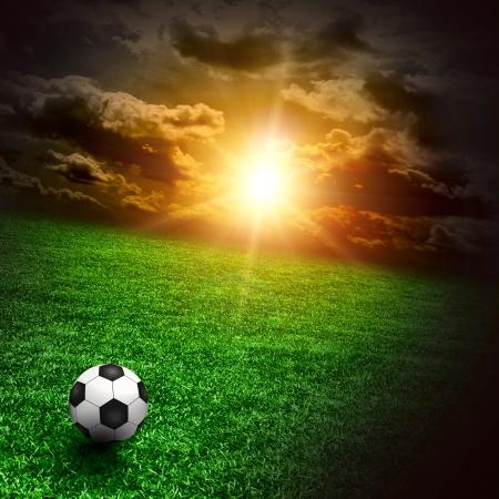 cancha de futbol: Un prado verde con un buen bal�n de f�tbol sobre todo en cielo del atardecer