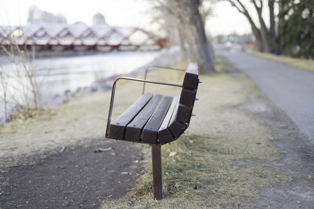 Park bench with bridge in background by river