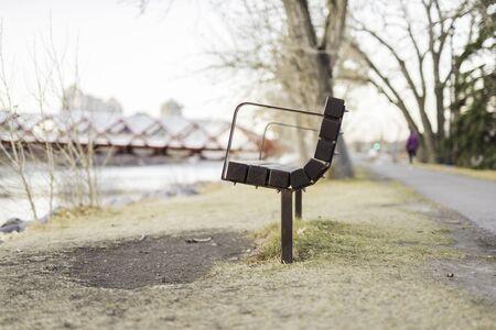park bench by river side with peace bridge in background Reklamní fotografie