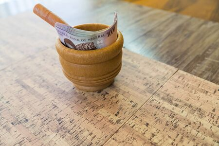 Mortar and Pestle with Nigerian Naira Inside Stock Photo