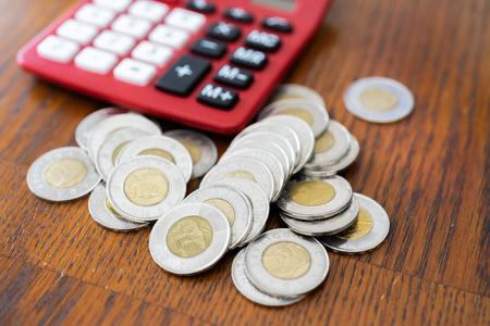 Calculatrice rouge avec des pièces au premier plan comptant de l'argent Banque d'images