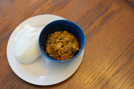 Nigerian Pounded Yam Served with Egusi Soup in Blue Bowl