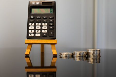 Black Calculator on Easel with Pile of Coins and Reflection 版權商用圖片