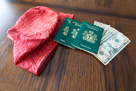 Nigerian Fila hat with Nigerian Passport and United States Dollars Stock Photo