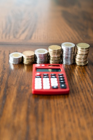 Red Pocket Calculator with Stacks of Coins in the background
