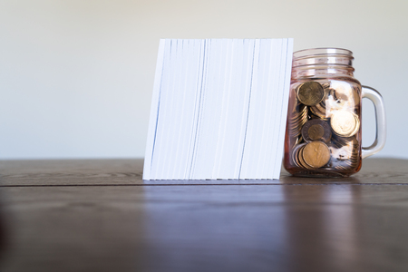 A jar full of coins used as a bookend for a stack of Notebooks