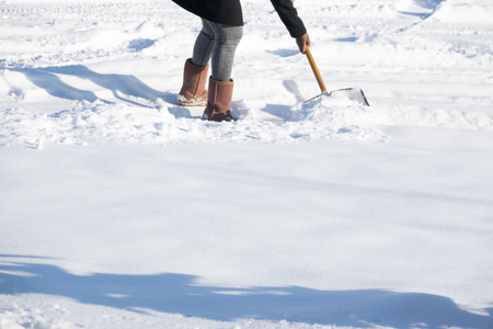 Woman shovelling snow to clear her driveway after winter storm Stock Photo