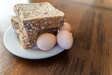 Brown fresh Eggs and Slices of Whole grain bread on white plate Stock Photo - 115602261