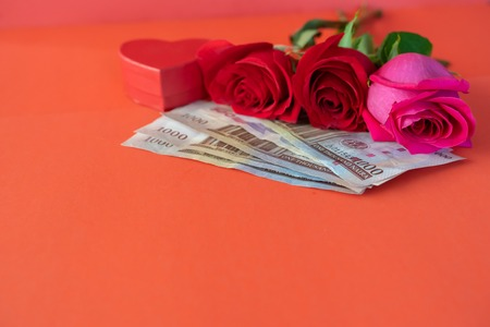 Fresh cut red roses with Nigerian Naira notes for valentines