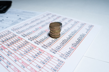 Stack of Coins with Calculator and finacial report Spreadsheet - business concept