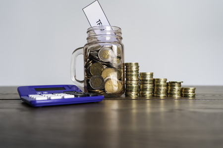 Jar of Coins with calculator showing savings to a Tax Free Savings Account