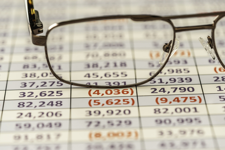 Reading glasses used to review spreadsheet report Stock fotó