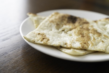 Pieces of Indian Nann bread on white plate