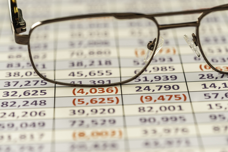 Reading glasses used to review spreadsheet report Banco de Imagens