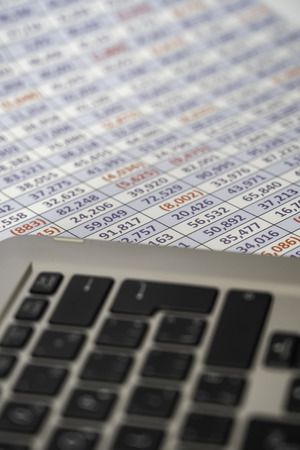 laptop keyboard with spreadsheet in the background