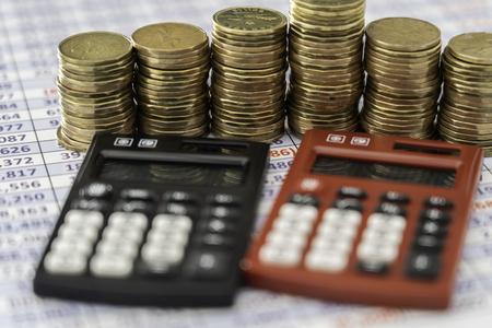 coins stacks with red and black Calculators in front