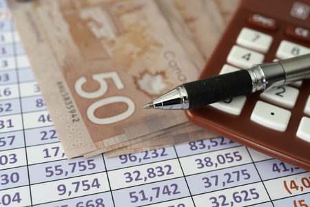 Canadian Dollar Notes on spreadsheet with Calculator with pen