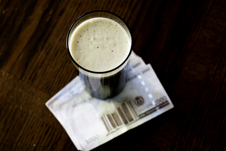 A glass of beer with Nigerian Naira Notes in a bar