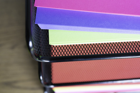 stack of documents on brightly colored paper on stacked tray on office table