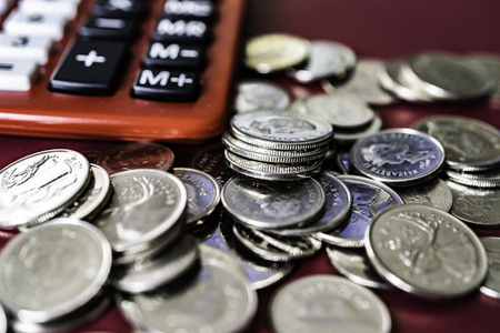 Red table top calculator with Silver coins