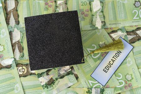 University Mortarboard academic cap on Canadian Dollar notes 写真素材