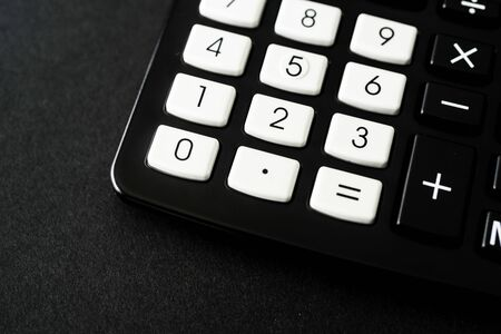 Black Pocket Calculator in office on black background Stock Photo