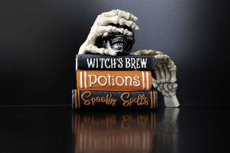 Halloween Skeleton hands holding magic books for Halloween