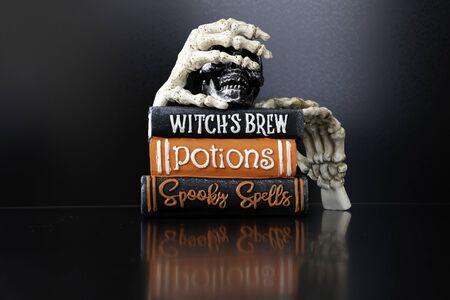 Manos de esqueleto de Halloween sosteniendo libros mágicos para Halloween Foto de archivo