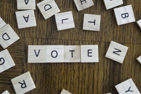 VOTE spelled out in wood letter tiles