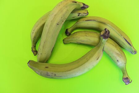 Nigerian Green unripe plantains on a green background