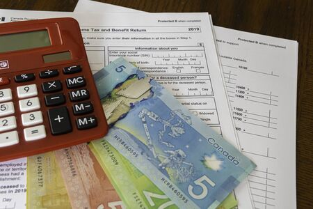 Calculator with Canadin Dollar notes and Canadian new 2019 Tax Form